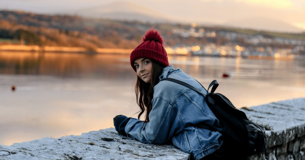 Girl in red bobble hat on harbour