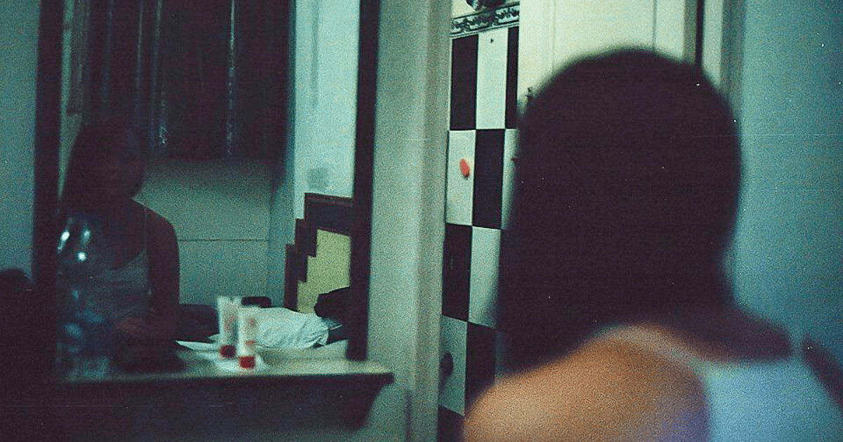 Girl looking in a hostel mirror with acne