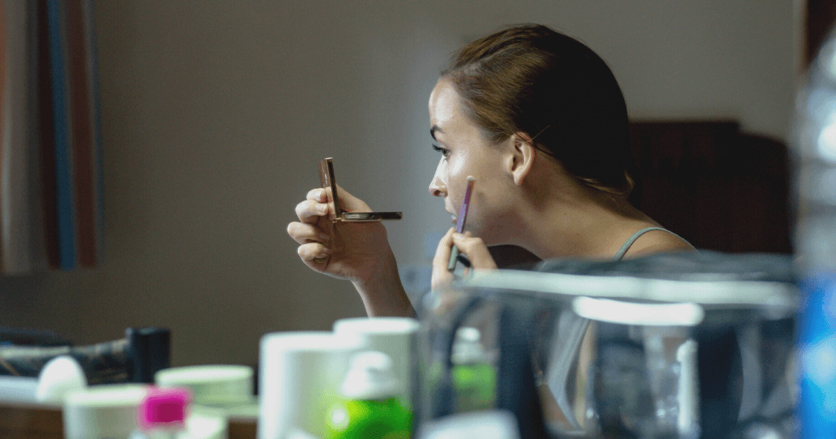 Girl with acne putting makeup on mirror