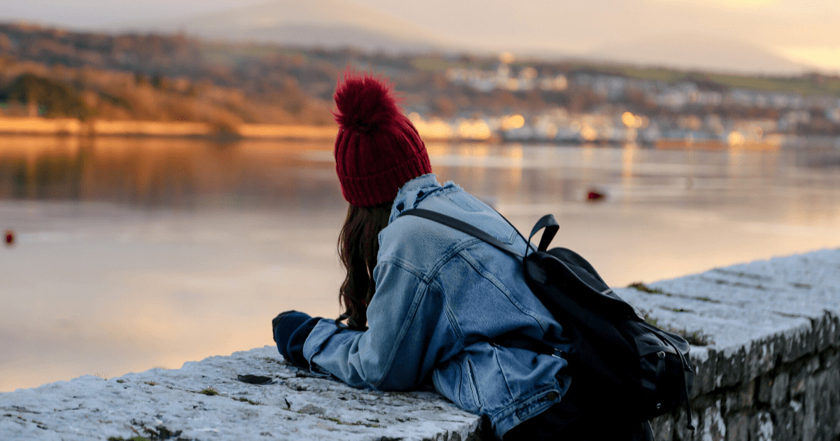 Girl with red bobble hat looking at menai straits